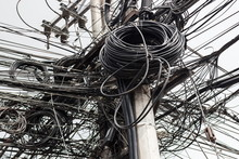 Background Of Chaotic Electrical Wires On The Concrete Pillar. Disorderly Connection Of Wires And Cables In Philippines. Power Cords And Telephone Lines Are Installed On Electricity Pole With Clutter