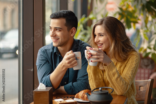 Photographie  Young couple in love sitting in a cafe, drinking coffee
