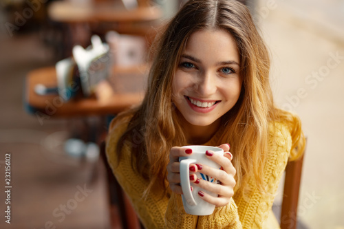 Young charming woman having coffee in a coffee shop