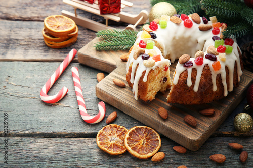 Fotografía  Bundt cake with candy cane and dried oranges on wooden table