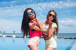 Two attractive girls with long hair are posing near pool on the sun. Brunette girl wears short pink shorts and T-shirt, blond wears yellow shorts and T-shirt. They are sending a kiss to the camera.