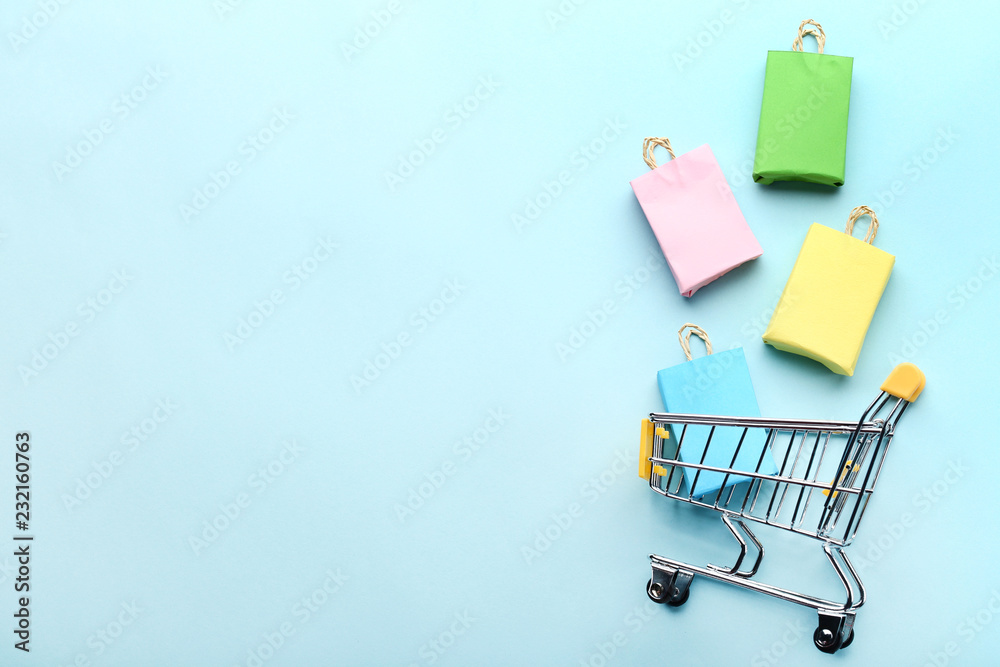 Fototapeta Small paper shopping bags with shopping cart on blue background