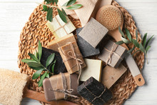 Wicker Mat With Handmade Soap Bars, Brush And Olive Leaves On Table, Top View