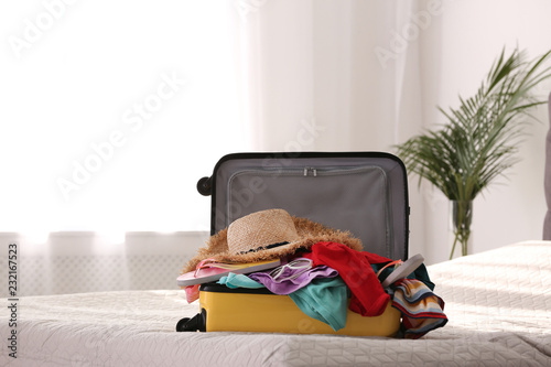 Modern suitcase full of clothes on bed indoors. Space for text