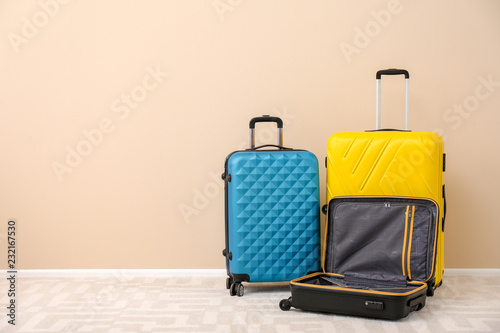 Modern suitcases on floor near light wall. Space for text Wallpaper Mural