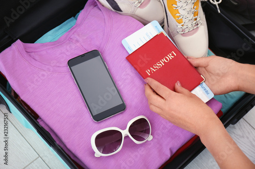 Woman packing suitcase for journey, closeup view