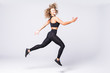 Full length picture of fitness woman jumping over gray background