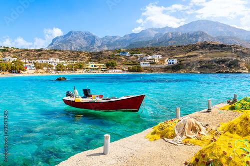 Fotografia  Boat on sea in Lefkos port with fishing nets on shore, Karpathos island, Greece