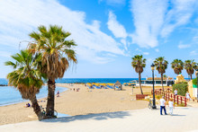 MARBELLA TOWN, SPAIN - MAY 12, 2018: Couple Of Tourists Walking On Coastal Promenade Along Beach In Marbella Seaside Town. Southern Spain Is Popular Holiday Destination In Europe.