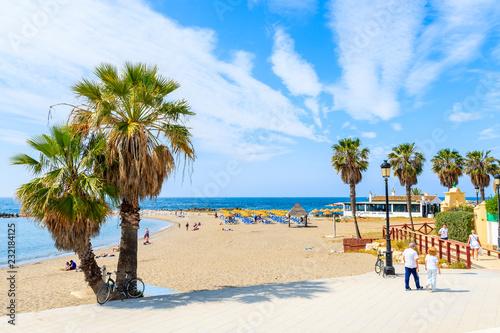 Obraz na płótnie MARBELLA TOWN, SPAIN - MAY 12, 2018: Couple of tourists walking on coastal promenade along beach in Marbella seaside town