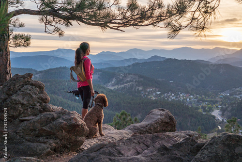 Leinwand Poster A hispanic woman is hiking with a dog, at sunset, in the Rocky Mountains near De