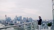 A portrait of businessman with laptop standing against London view panorama.