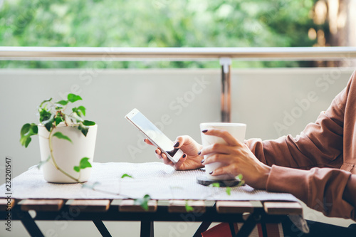 Obraz na plátně  Female drinks hot beverage and chats, reads social network, puts likes on cell phone after hard working day at home while sitting on the balcony with green view