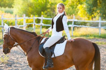 Fototapeta Girl equestrian rider riding a beautiful horse in the rays of the setting sun. Horse theme