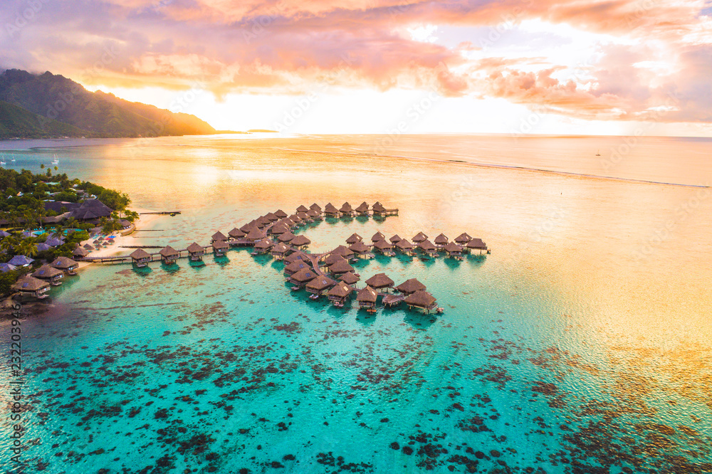 Fototapeta Luxury travel vacation aerial of overwater bungalows resort in coral reef lagoon ocean by beach. View from above at sunset of paradise getaway Moorea, French Polynesia, Tahiti, South Pacific Ocean.
