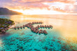 canvas print picture - Luxury travel vacation aerial of overwater bungalows resort in coral reef lagoon ocean by beach. View from above at sunset of paradise getaway Moorea, French Polynesia, Tahiti, South Pacific Ocean.