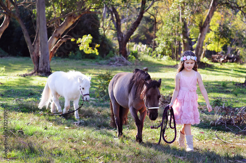 Cute little girl and pony in a beautiful park Wallpaper Mural
