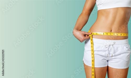 Obraz Slim young woman measuring her thin waist - fototapety do salonu