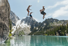 Young Men Jumping From Cliff I...