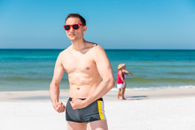 Man Muscular Standing On Beach Flexing Muscles During Sunny Day With Red Sunglasses In Florida With Ocean Water, People Walking