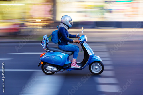 young woman with a scooter on the move in the city