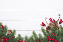 Christmas And New Year's Composition. Top View Of Spruce Branches, Pine Cones, Red Berries And Bell On White Wooden Table Background.