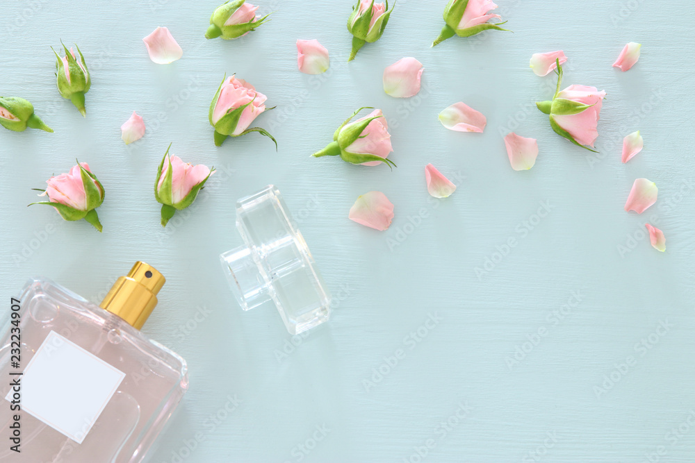 Fototapety, obrazy: Top view image of perfume bottle with rose petals flowers over pastel blue background. Floral scent concept.