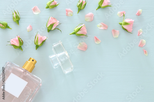 Obraz Top view image of perfume bottle with rose petals flowers over pastel blue background. Floral scent concept. - fototapety do salonu