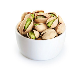Bowl with pistachios isolated on a white background.
