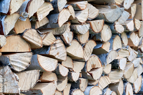 Large pile or stock of firewood for heating furnace. Logs and logs of birch. The log is split in half. Slice as a circle, semicircle. Background, backdrop, texture. Side view. Shallow depth of field.