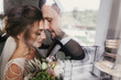 canvas print picture - Gorgeous bride and stylish groom gently hugging at window. Sensual wedding couple embracing. Romantic moments of newlyweds. Creative wedding photo through glass. Copy space