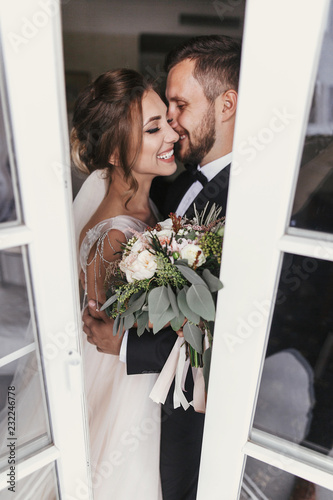 Fotografia Gorgeous bride and stylish groom gently kissing at window