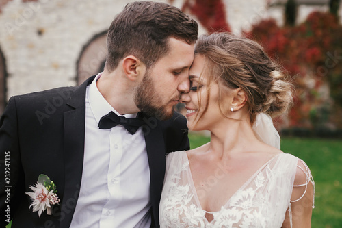 Stampa su Tela Gorgeous bride and stylish groom gently hugging and kissing outdoors