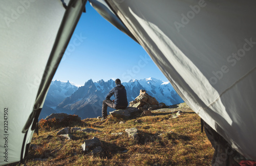 Hiker enjoying the mountain view in front of his tent Fototapet