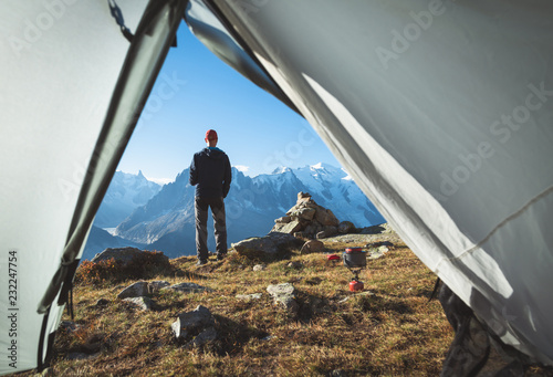Photo Hiker enjoying the view and a cup of coffe at his campsite in the mountains