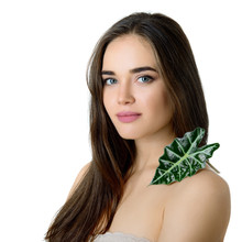 Gorgeous Girl With Cleann Skin And Perfect Hair Holding Green Fresh Leaf On Her Shoulder, Studio Shot Isolated On White Background. Beautiful Young Woman's Portrait. Care Of Mother-nature.