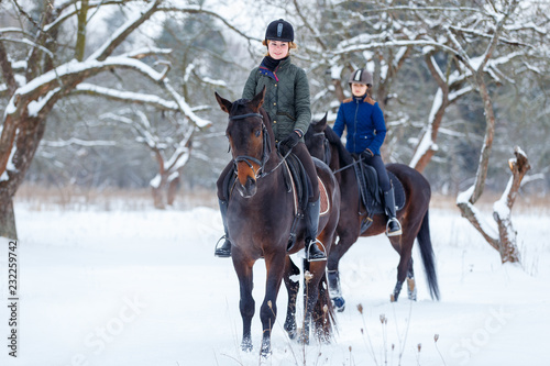 Two young women riding horses in winter park Fototapeta