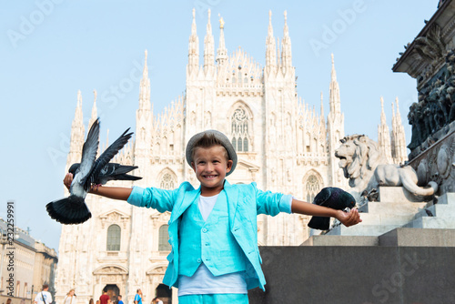 Young boy posing with pigeons in the milanese street with ancient church Duomo di Milano on background Canvas Print