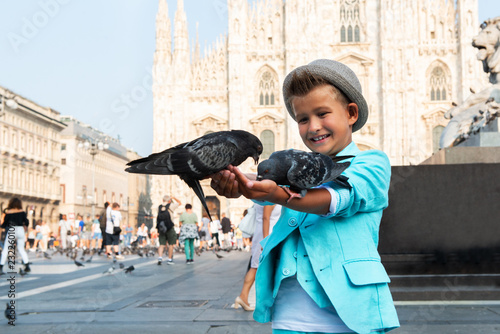 Photo  Young boy posing with pigeons in the milanese street with ancient church Duomo di Milano on background