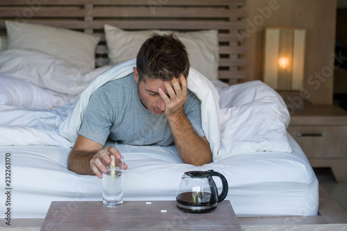 Poster de jardin Bar lifestyle home portrait of young exhausted and wasted man waking up suffering headache and hangover after drinking alcohol at night party lying on bed sick