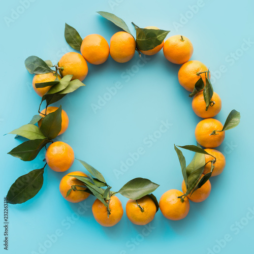 Wreath of fresh mandarin with leaves on blue punchy pastel. Top view. Fruits pattern.