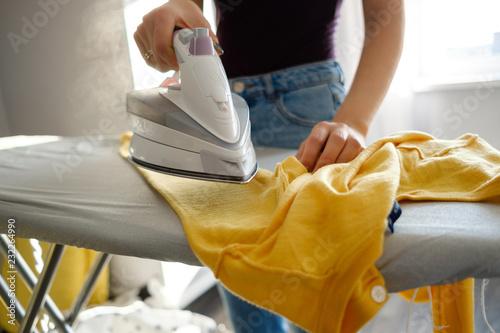 Obraz na plátně Girl ironing clothes  at home a yellow jacket