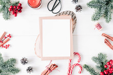 Christmas Composition. Christmas Card Mockup Gift, Vintage Scissors, Candy, Red Berries, Vanilla Sticks, Pine Cones, Fir Branches On Wooden White Background. Flat Lay, Top View, Copy Space
