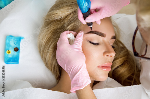 Obraz Beautiful woman with smooth, young skin, sitting in a beautician. A beautician performs modeling permanent eyebrows makings.Permanent makeup treatment. - fototapety do salonu