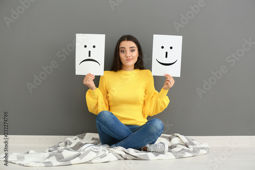 Cuadros en Lienzo Emotional woman holding sheets of paper with drawn emoticons while sitting near