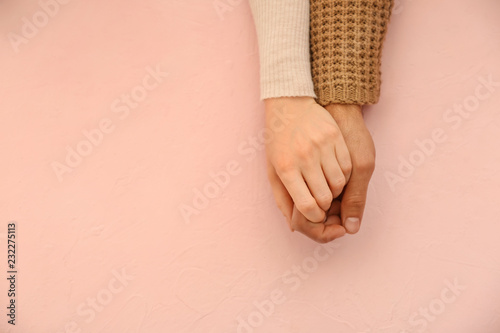 Loving young couple holding hands on color background Fototapet