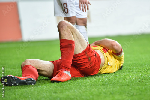 In de dag Hert The injured footballer lies on the pitch and the opponent player extends his hand towards him.