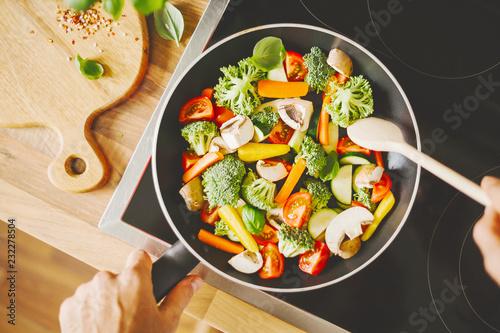 Fototapeta Man cooking fresh vegetables on pan obraz