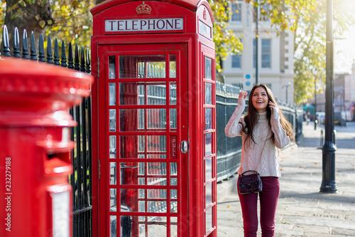Fotografie, Obraz  Touristin in London steht vor einer roten Telefonzelle und telefoniert mit ihrem