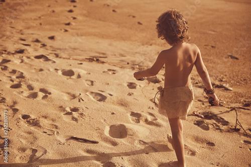 Photo  Little mowgli boy walking on sand beach. Sunset light